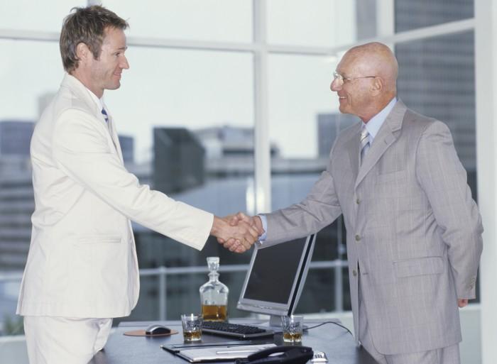 2 אנשי עסקים בחליפות לוחצים ידיים