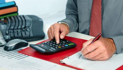 ידיו של רואה חשבון בזמן הקלדה על מחשבון
