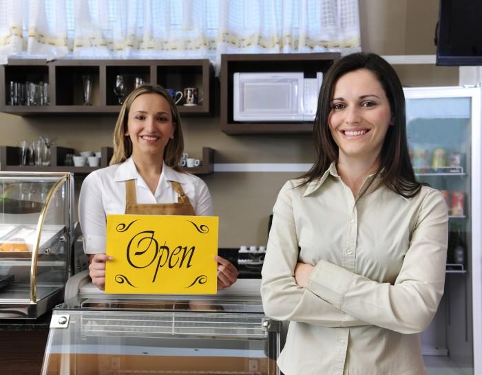 """שתי נשים מחייכות עומדות בחנות כשאחת מהן מחזיקה שלט צהוב עם הכיתוב """"OPEN"""""""