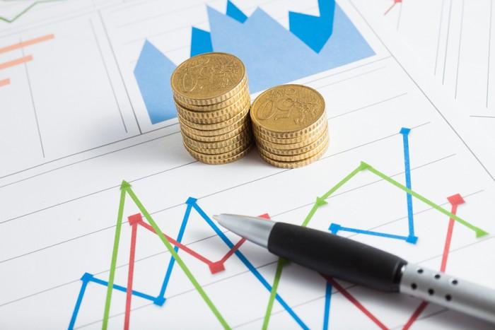 מגדל מטבעות על גבי ניירות שמציגים גרפים פיננסיים