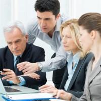 קבוצה של חשבי שכר בכירים מדיינים לגבי נתונים שמוצגים על גבי מסך של מחשב נייד