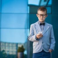 ילד לבוש כמנהל חשבונות ובידו טלפון נייד