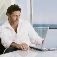 גבר בחולצה לבנה יושב מול מחשב נייד על רקע ים