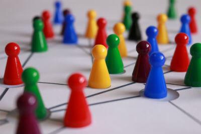 חיילי משחק צבעוניים על גבי לוח משחק כדימוי לנטוורקינג